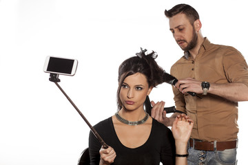 girl making selfie while hairdresser blow-dry her hair