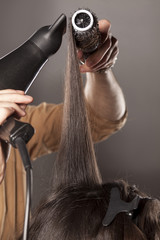 hairdresser doing his client hair with a hair drier and comb