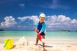 Little boy having fun on the beach while building a sand castle