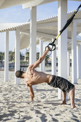 Young man athlete doing cross training workout at the beach