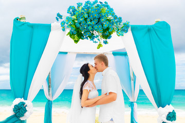 Wedding ceremony on a tropical beach in blue. Happy groom and br