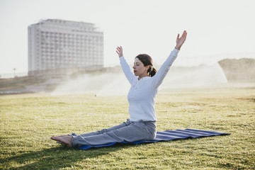 Young woman doing yoga on the grass