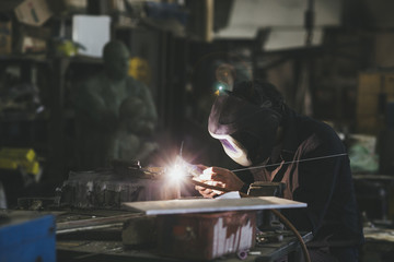Man with mask welding in a workshop