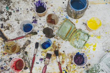 Paint in cups with dry brushes shot from above