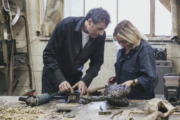 Two artists examining a sculpture in a workshop