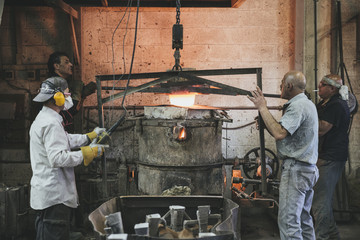Four man using a small crane to lift a furnace
