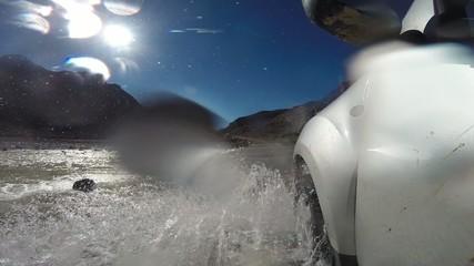 4wd car wades a river in Atlas Mountain, Morocco