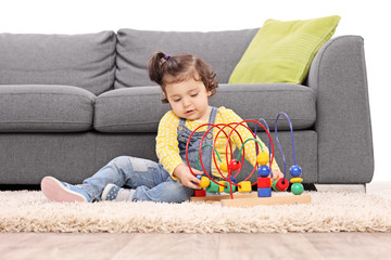 Cute little girl playing with a toy seated on the floor