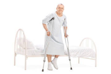 Mature patient with crutches getting out of bed