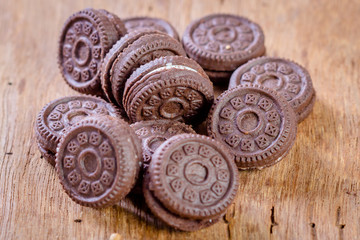 Chocolate cookies with cream on wooden table