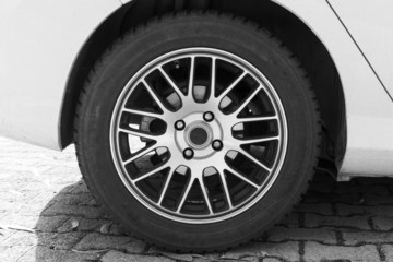 White modern car fragment with wheel on steel disc