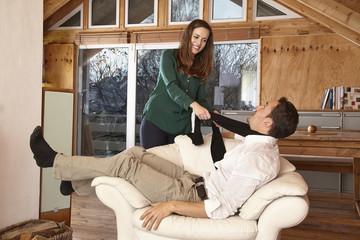 Paar zuhause, Frau zieht am Schal des Mannes