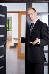 Estate agent stands at the entrance to apartment
