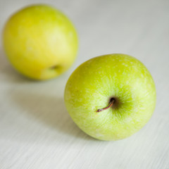 green apples on white wooden background
