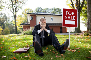 Tired estate agent is sitting on grass