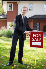 Estate agent holding sign outside