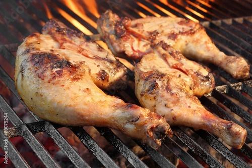 Leinwandbild Motiv Marinated Chicken Legs Fried On The Hot Flaming BBQ Grill