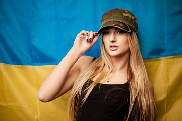 Woman in khaki cap against Ukrainian flag