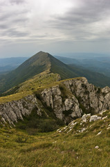 Rocks and cliffs under dark clouds at Suva Planina mountain
