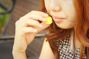 Woman eating a macaron at the park.