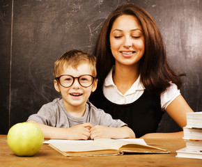 little cute real boy with teacher in classroom at desk close up
