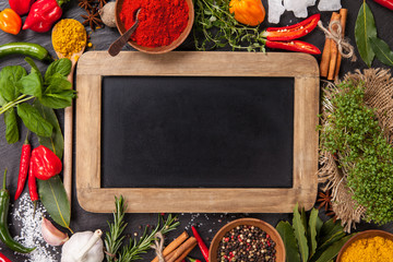Various spices on stone with blackboard