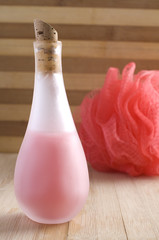 Bottle of Pink Bath Soap with Red Sponge on Wood