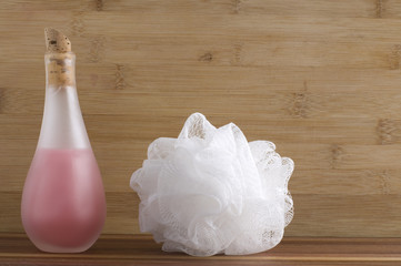 Bottle of Pink Bath Soap with White Sponge on wood