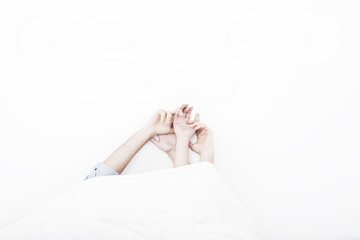 Young couple laying in bed with hands raised in the air