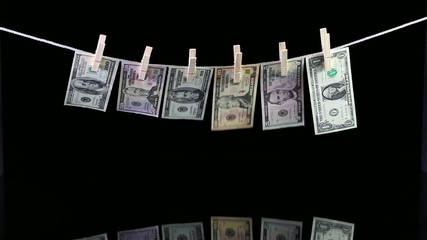 Dirty US dollar banknotes hanging from a clothesline