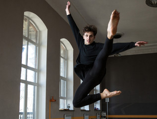 Young male dancer jumping at gym