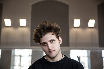 Portrait of a young serious man with curly hair