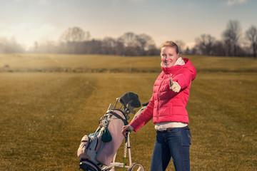 Lächelnde Golferin macht Daumen hoch