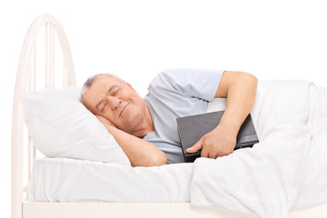 Senior sleeping in a bed and holding a book