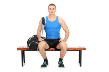 Sportsman sitting on a wooden bench