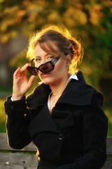 Ragazza che si toglie gli occhiali da sole al parco