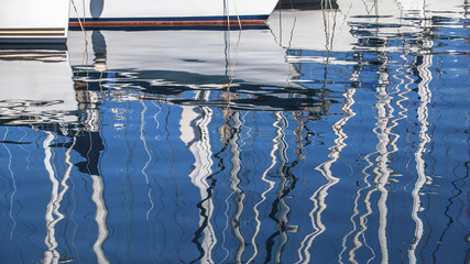 Reflection of yacht masts in the water of the Harbor. Luxury.