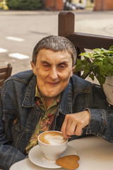 Portrait of elderly disabled man with cerebral palsy, at cafe.
