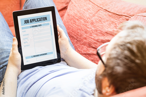 Leinwanddruck Bild hipster on the sofa with job application tablet