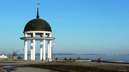 Rotunda on quay and landscape of icy lake in spring