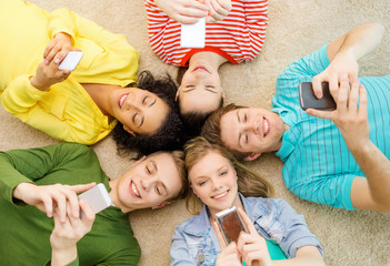 group of smiling people lying down on floor