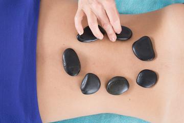 Adult woman having hot stone massage