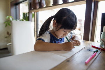 Girl with pigtails sitting at a table, drawing with felt tip pens.