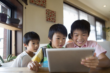 Three boys sitting at a table, looking at a digital tablet, smiling.