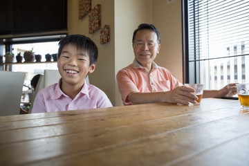 Man and boy sitting at a dining table, smiling.