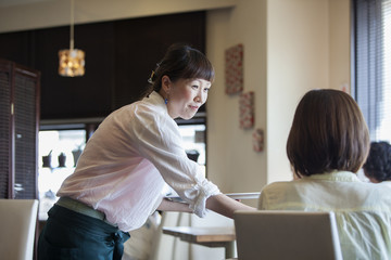 Waitress serving a woman seated at a table in a cafe.