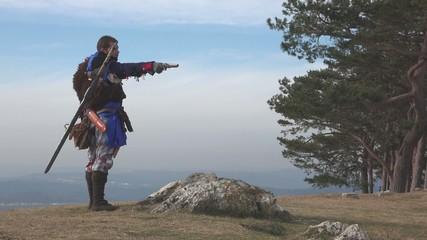 Assasin drawing pistol on mountain