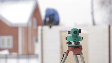 Land surveyor total station against the background of a wooden
