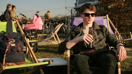 Student sitting on sunbed and drinking beer outdoors