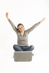 Happy woman sitting on floor with a laptop and arms raised up